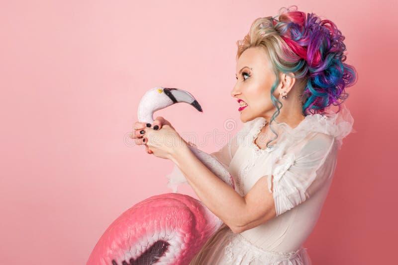Mulher à moda e bonita com cabelo colorido Estrangula uma figura cor-de-rosa do flamingo imagem de stock