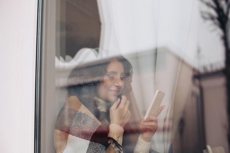 Mulher à moda em um batom vestindo do café que olha no espelho, coberto com uma cobertura, fria Cabelo longo, menina atrás imagens de stock royalty free
