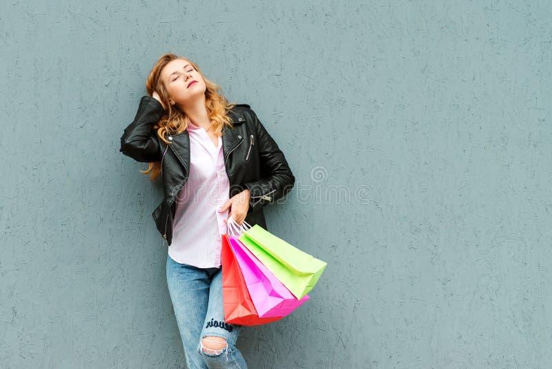 Mulher à moda feliz com os sacos de compras sobre o fundo cinzento Jovem mulher bonita que aprecia na compra Consumição, compra,  foto de stock
