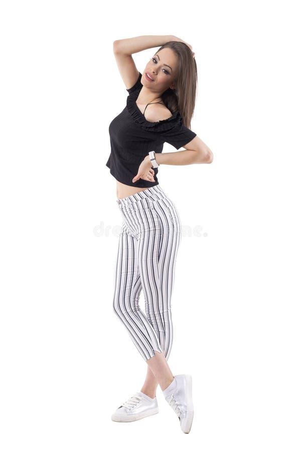 Mulher à moda lindo da beleza do modelo de forma que levanta com mão no cabelo que olha a câmera foto de stock royalty free