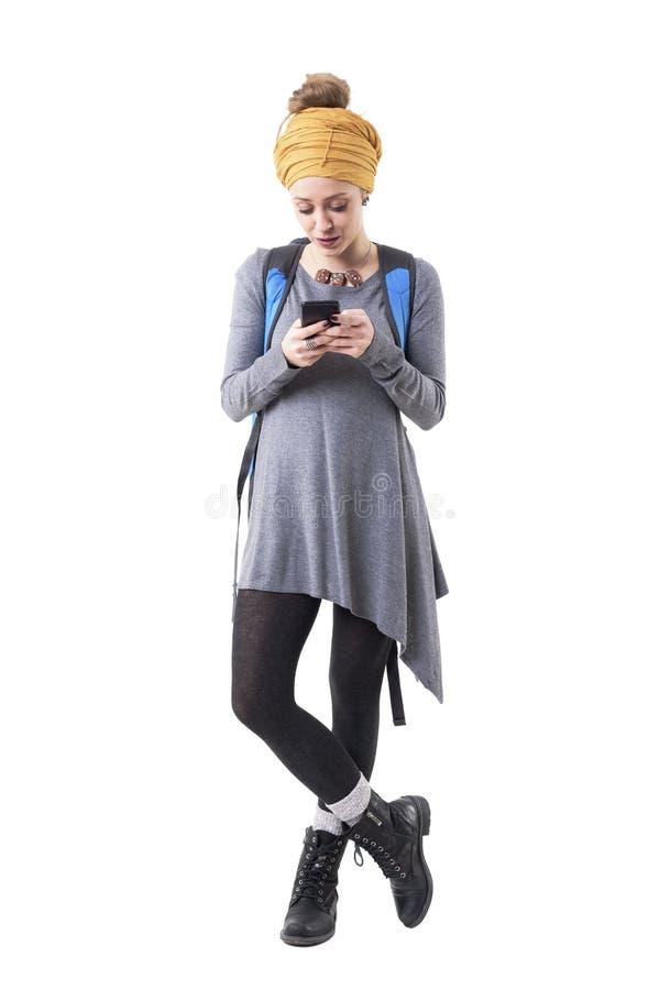 Mulher à moda moderna fresca do viajante do moderno com mensagens da leitura da mochila no telefone celular imagens de stock royalty free