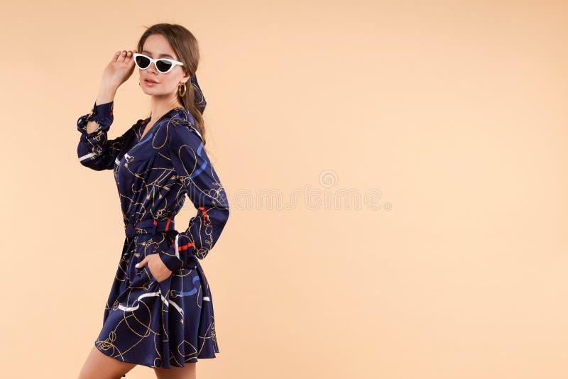 Mulher à moda no vestido azul e nos vidros que levantam no estúdio fotos de stock