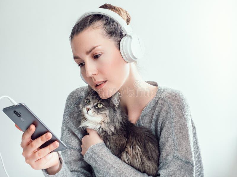 Mulher à moda nos fones de ouvido e com seu gatinho imagens de stock