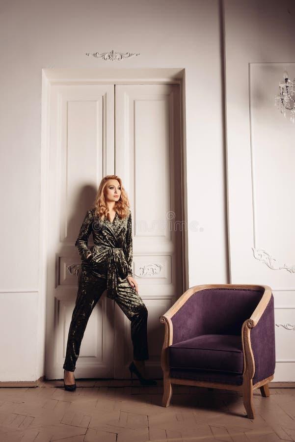Mulher à moda nova bonita que está a poltrona próxima foto de stock