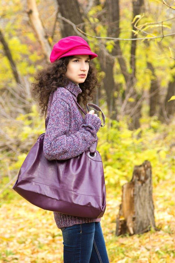 Mulher à moda nova com um saco grande no parque do outono imagem de stock