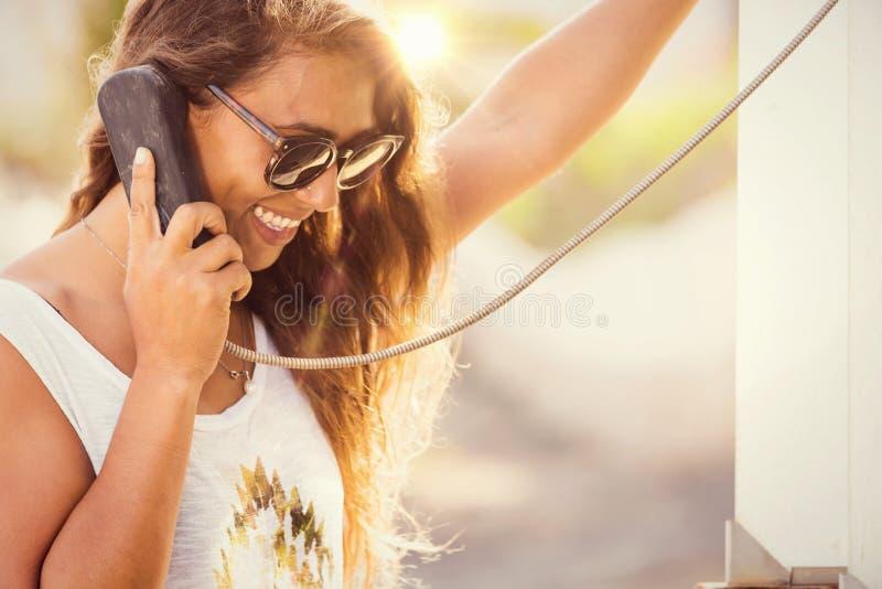 Mulher à moda nova na caixa de telefone estilo retro da conversa do telefone foto de stock royalty free
