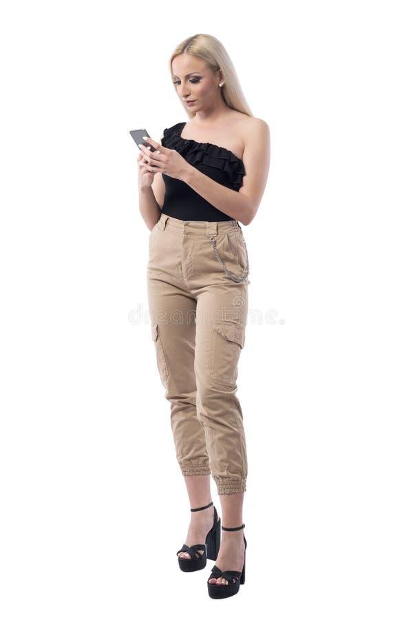 Mulher à moda nova relaxado da forma que usa meios sociais no telefone esperto imagens de stock royalty free