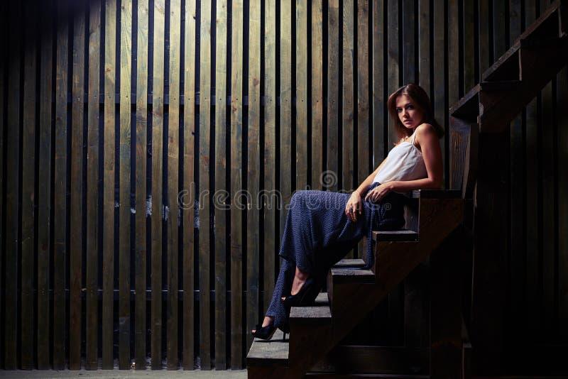 Mulher à moda nova surpreendente que senta-se em escadas e que olha a came imagens de stock royalty free