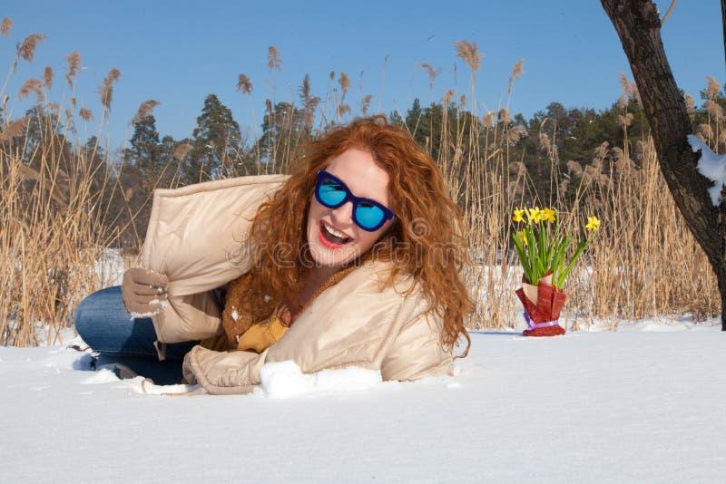 Mulher à moda otimista que olha o através dos óculos de sol azuis ao encontrar-se na neve fotos de stock royalty free