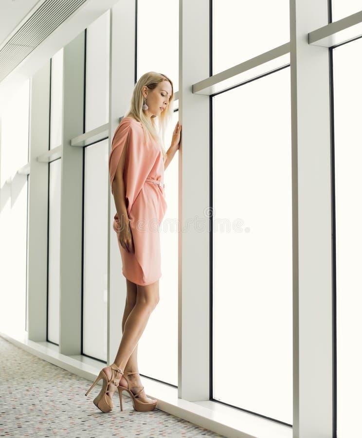 mulher à moda perto da janela no prédio de escritórios fotos de stock royalty free