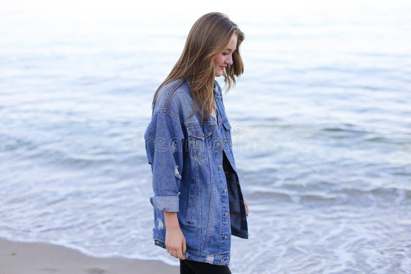 A mulher à moda pisa seguramente ao longo do litoral e as poses entraram imagem de stock