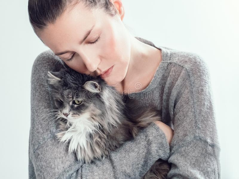 Mulher à moda que abraça delicadamente seu gatinho imagens de stock royalty free