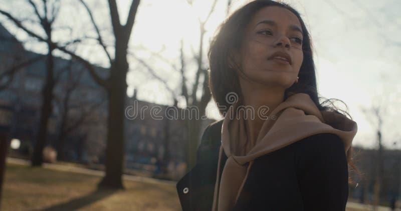 Mulher à moda que relaxa em um parque da cidade durante o dia ensolarado imagens de stock royalty free