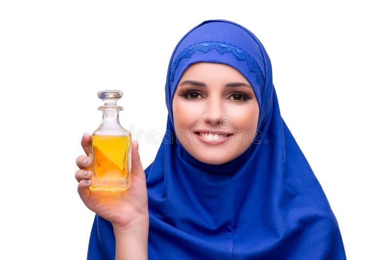 A mulher árabe com a garrafa do perfume isolada no branco foto de stock