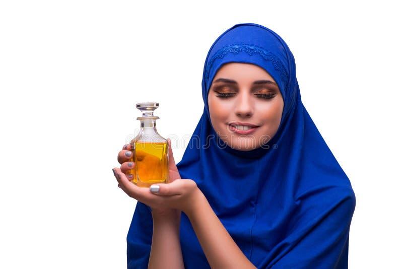 A mulher árabe com a garrafa do perfume isolada no branco imagem de stock