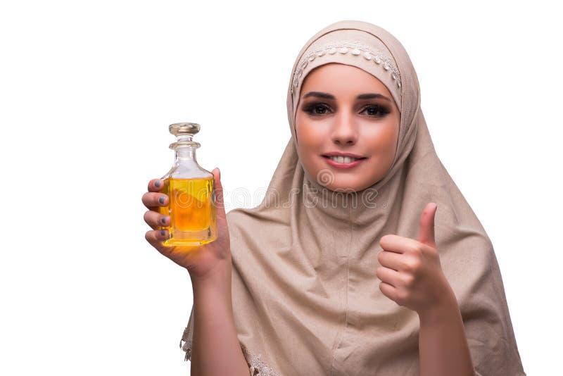 A mulher árabe com a garrafa do perfume isolada no branco fotos de stock