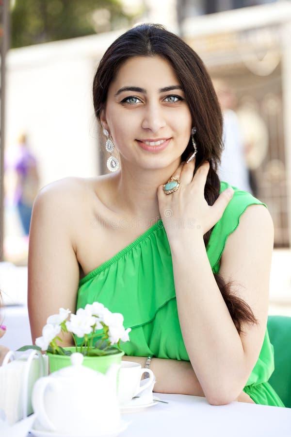 Mulher árabe consideravelmente nova que senta-se no café fotos de stock royalty free