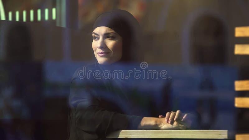 Mulher árabe de sorriso que olha a cidade através da janela que senta-se no café, lazer fotos de stock