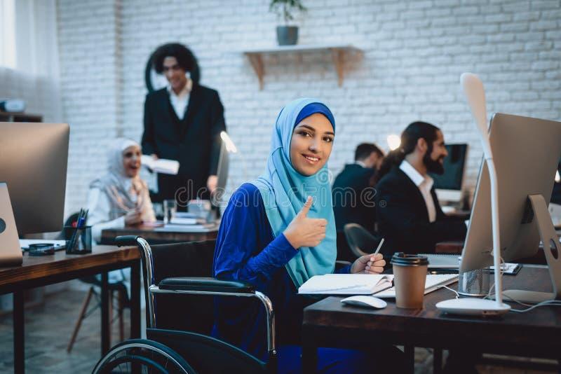 Mulher árabe deficiente na cadeira de rodas que trabalha no escritório A mulher está dando os polegares acima imagens de stock