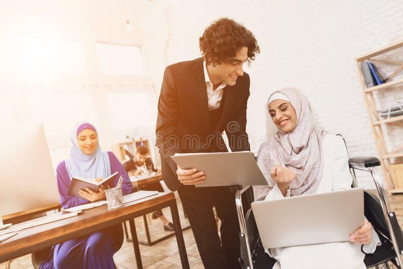 Mulher árabe deficiente na cadeira de rodas que trabalha no escritório A mulher está falando ao colega de trabalho masculino imagem de stock