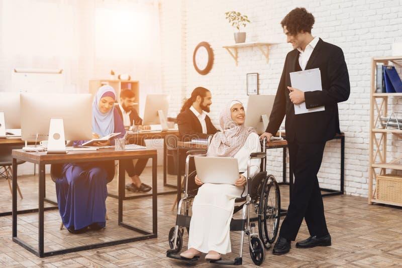 Mulher árabe deficiente na cadeira de rodas que trabalha no escritório A mulher está falando ao colega de trabalho masculino fotos de stock