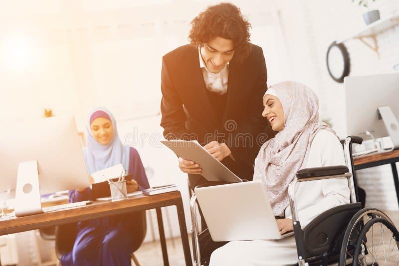 Mulher árabe deficiente na cadeira de rodas que trabalha no escritório A mulher está falando ao colega de trabalho masculino imagens de stock