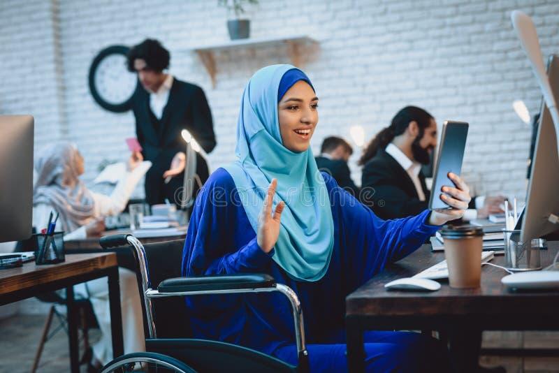Mulher árabe deficiente na cadeira de rodas que trabalha no escritório A mulher está falando na tabuleta imagem de stock royalty free