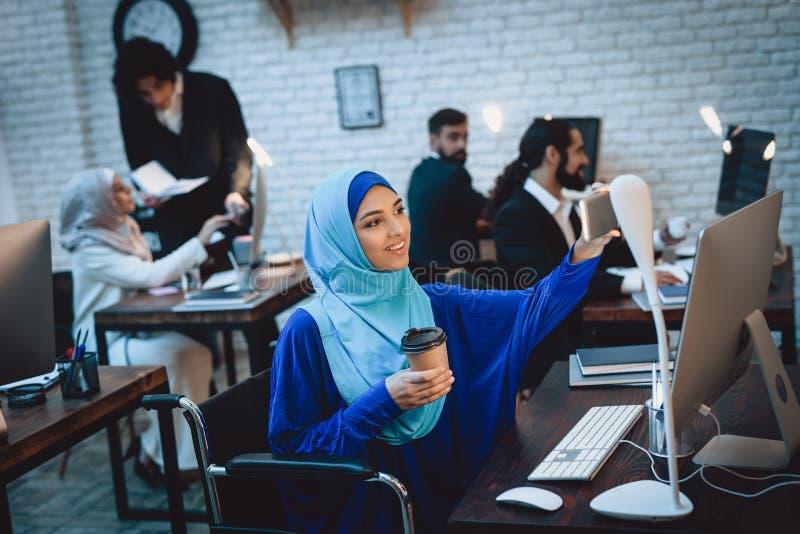 Mulher árabe deficiente na cadeira de rodas que trabalha no escritório A mulher está tomando o selfie fotografia de stock royalty free