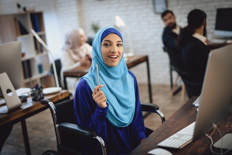 Mulher árabe deficiente na cadeira de rodas que trabalha no escritório A mulher está trabalhando no computador de secretária imagem de stock