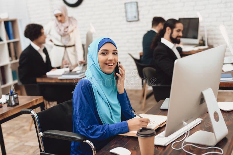 Mulher árabe deficiente na cadeira de rodas que trabalha no escritório A mulher está trabalhando no computador de secretária e es fotografia de stock