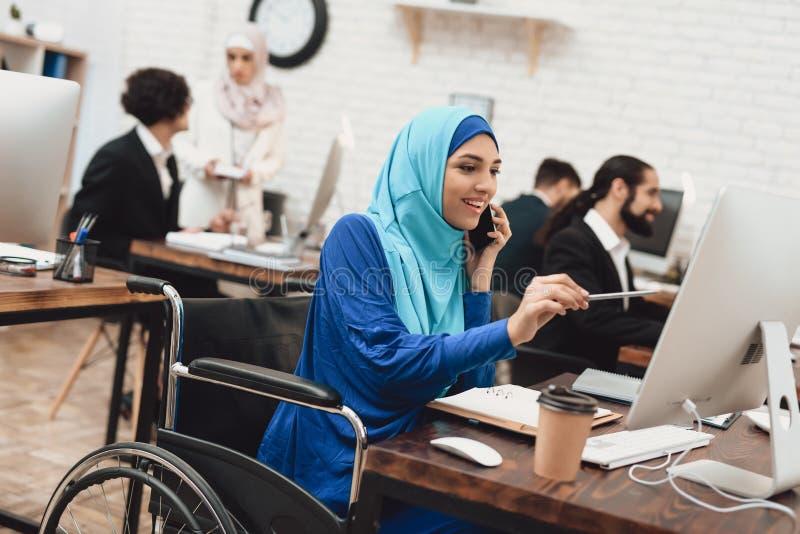 Mulher árabe deficiente na cadeira de rodas que trabalha no escritório A mulher está trabalhando no computador de secretária e es imagem de stock royalty free