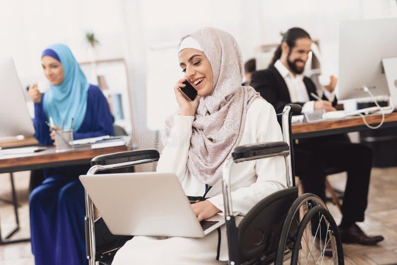 Mulher árabe deficiente na cadeira de rodas que trabalha no escritório A mulher está trabalhando no portátil e está falando no te fotografia de stock royalty free