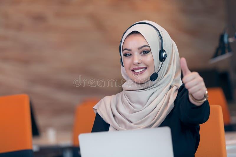Mulher árabe do operador bonito do telefone que trabalha no escritório startup imagem de stock royalty free