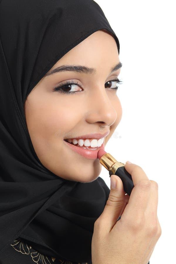 Mulher árabe dos emirados do saudita que pinta seus bordos com um batom fotografia de stock royalty free