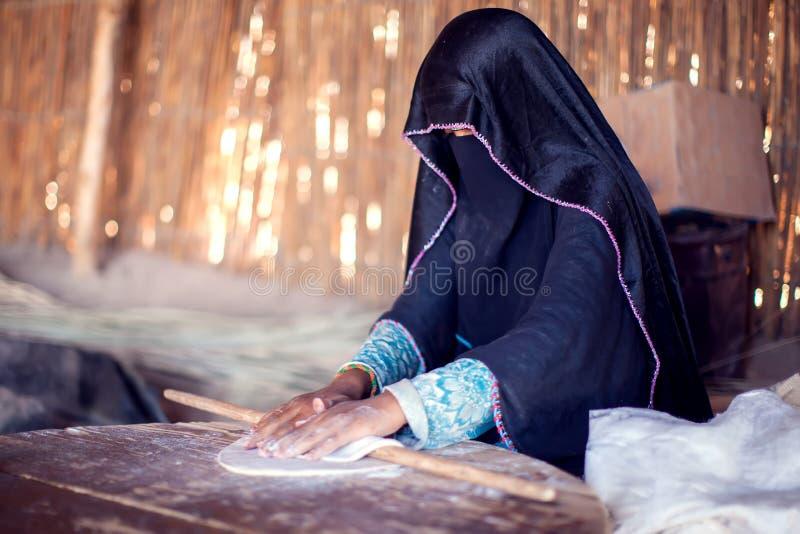 A mulher árabe faz o pão na vila beduíno em Egito fotografia de stock