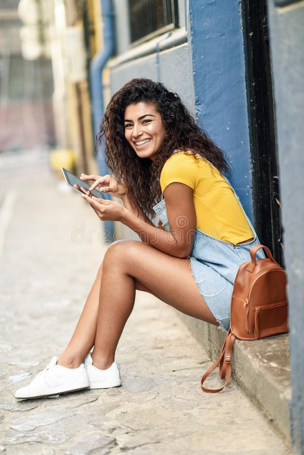 Mulher árabe feliz que senta-se na etapa urbana com uma tabuleta digital Menina africana que veste a roupa ocasional Viajante nov foto de stock