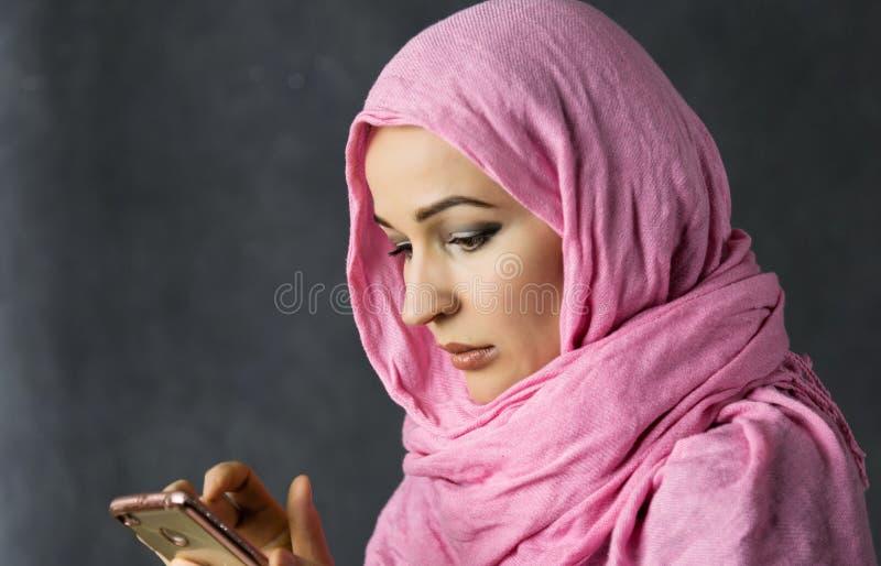 A mulher árabe muçulmana bonita recebe a mensagem do texto no smartphone fotografia de stock