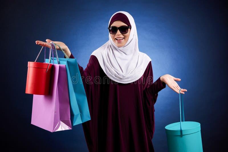 A mulher árabe nos óculos de sol guarda os sacos coloridos de papel foto de stock