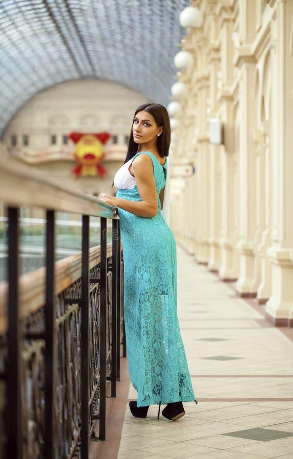 Mulher árabe nova no vestido do verde longo na loja foto de stock