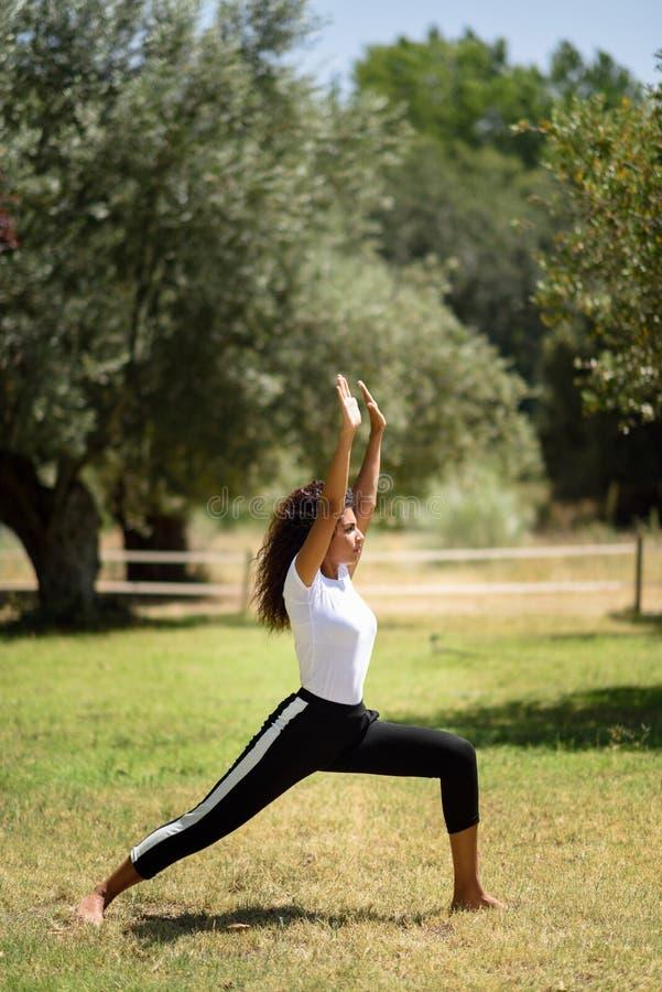 Mulher árabe nova que faz a ioga na natureza imagem de stock