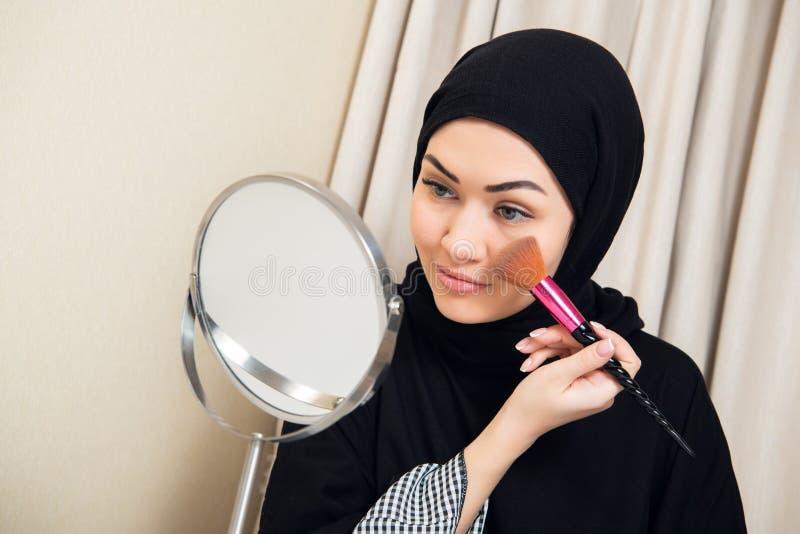 Mulher árabe que aplica a composição em sua cara, vestido árabe tradicional vestindo imagens de stock