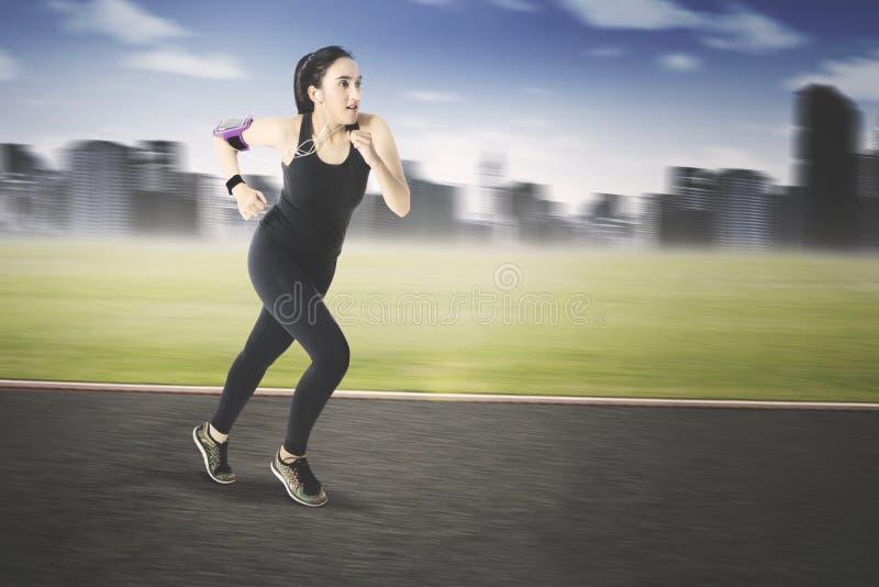 Mulher árabe que corre na estrada imagens de stock royalty free