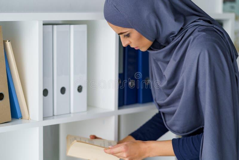 Mulher árabe que lê um livro fotografia de stock