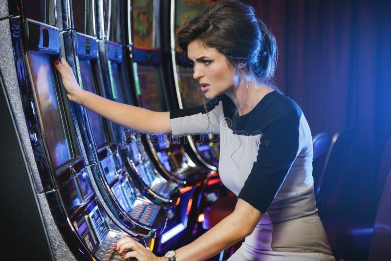 A mulher é perdedora durante o jogo dos slots machines fotos de stock royalty free