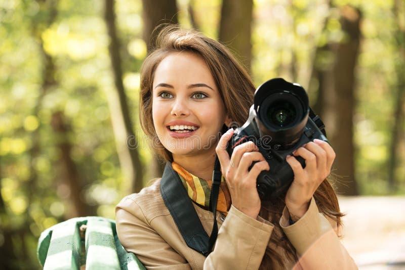 A mulher é um fotógrafo profissional com câmera da foto foto de stock royalty free