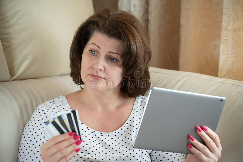 A mulher é virada pela compra em linha com um cartão de banco imagem de stock
