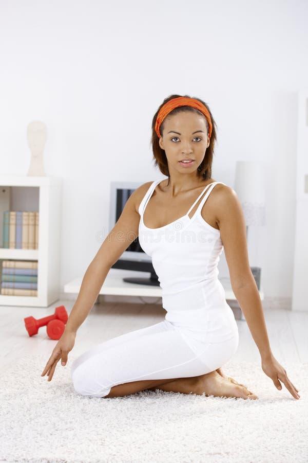 Mulher étnica atrativa que exercita em casa fotos de stock