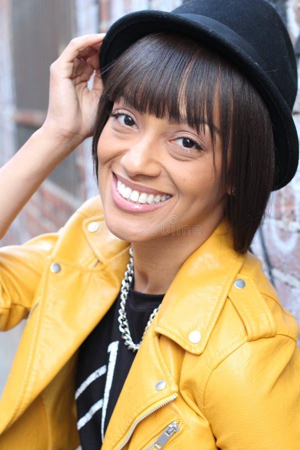 Mulher étnica com o chapéu tocante do sorriso toothy e o casaco de cabedal amarelo vestindo fotografia de stock