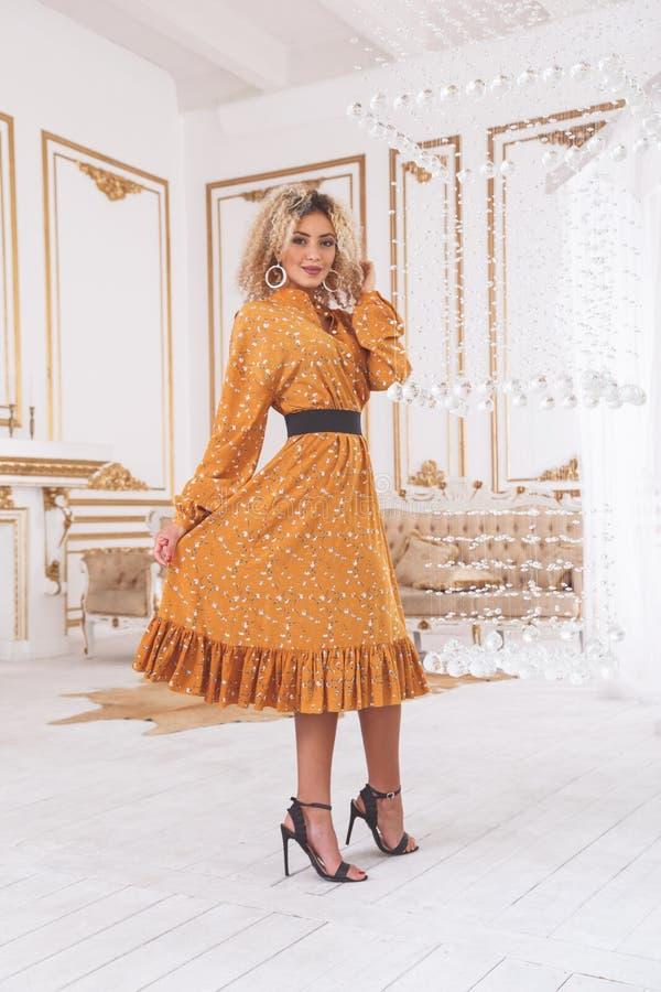 Mulher étnica encantador bonita no vestido que está no interior elegante foto de stock