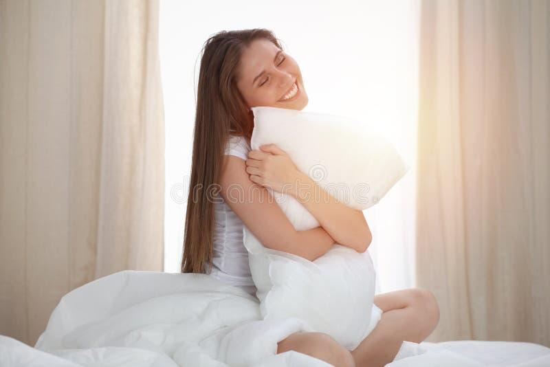 A mulher abraça o descanso após acorda, incorporando um dia feliz e relaxado após a boa noite de sono Sonhos doces, bom dia imagens de stock royalty free